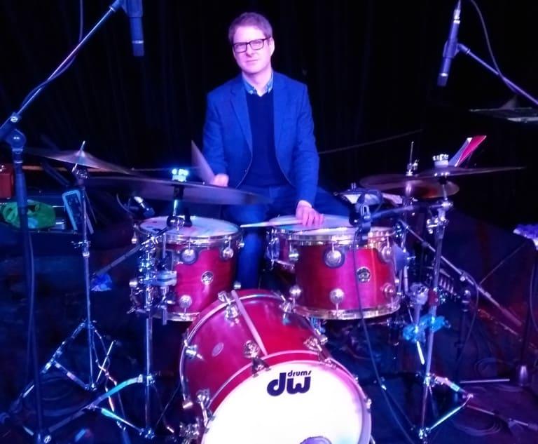 man sitting behind drum kit